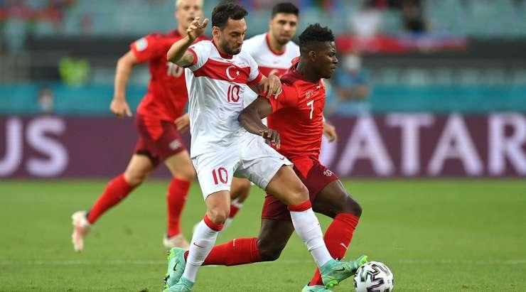 Hakan Çalhanoğlu (Türkiye) rakibini topu elinden alıyor, ancak hakem faul düdüğünü çalıyor.  Karardan memnun değil!