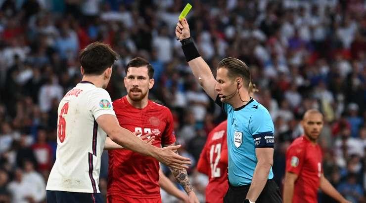 Danny Makkelie, bariz faulünden dolayı Harry Maguire'a (İngiltere) sarı kart gösteriyor.